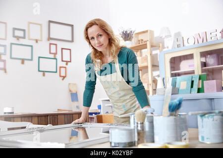 Portrait zuversichtlich Künstlerin Malerei Spiegel in art studio - Stockfoto