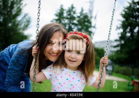 Junge Mutter spielt in der Spielplatz mit der kleinen Tochter. Frau schüttelt das Baby auf einer Schaukel. Stadt - Stockfoto