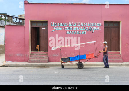Kubanische street scene, Hunde achten Sie bei man mit Karre zu Fuß durch, Hygiene Institut Matanzas, Cuba - Stockfoto