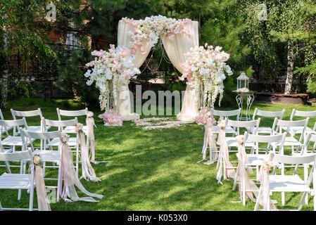 Hochzeit Bogen mit Tuch und Blumen im Freien eingerichtet. Schöne Hochzeit eingerichtet. Hochzeit auf grünen Rasen - Stockfoto