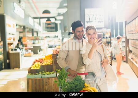 Lächelnde junge Paar unter selfie in Lebensmittelgeschäft Markt - Stockfoto
