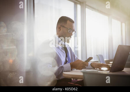 Ernsthafte Geschäftsmann SMS mit Handy mit Laptop im Büro - Stockfoto