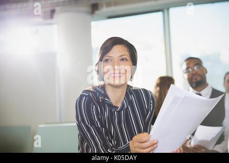 Lächelnd Geschäftsfrau mit Papierkram im Konferenzraum treffen - Stockfoto