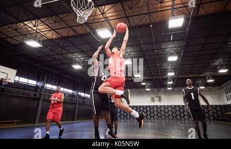 Junge männliche Basketballspieler Basketball spielen auf Gericht im Gymnasium - Stockfoto