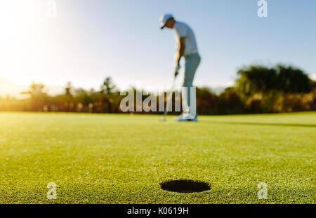 Golf Spieler die Kugel in Bohrung. Horizontale shot Golf Loch im grünen Feld mit Golfspieler im Hintergrund. - Stockfoto