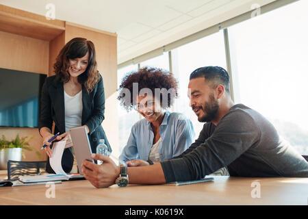 Multirassischen Geschäftsleute mit digitalen Tablet in Treffen im Büro. Business Leute, die auf der Suche nach Tablet - Stockfoto