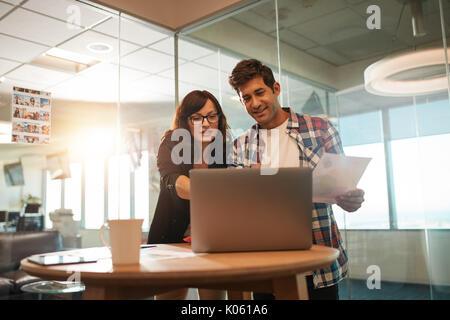 Junge Unternehmer und Geschäftsfrau zusammen arbeiten am Laptop im Büro. Paar kreative Arbeiten am neuen Projekt. - Stockfoto