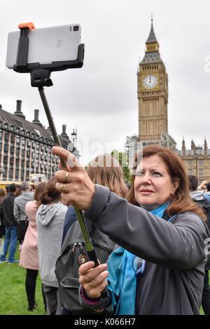 London, Großbritannien. 21 Aug, 2017. Eine Frau nimmt eine selfie vor dem Big Ben in London, Großbritannien am 12.08.21., - Stockfoto