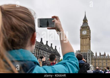 London, Großbritannien. 21 Aug, 2017. Eine Frau nimmt Fotos vor dem Big Ben in London, Großbritannien am 12.08.21., - Stockfoto