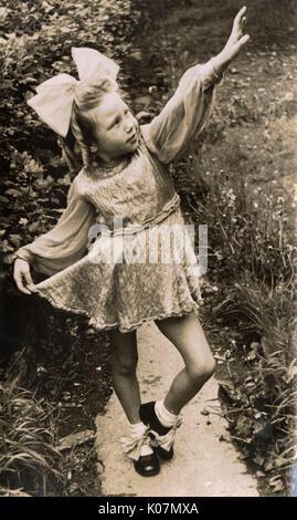 Kleine Mädchen in Tracht, auf einem Garten weg posieren. Datum: ca. 1930 s - Stockfoto