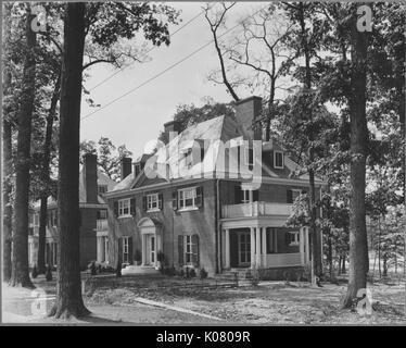 Abgewinkelte frontale Ansicht von zu Hause neben ruhigen Straße von großen Bäumen gesäumt, die Startseite erscheint - Stockfoto