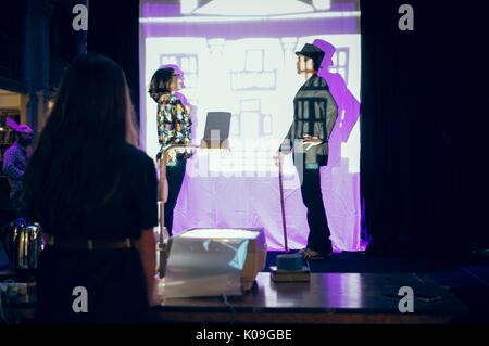 Ein Mann in Anzug und Hut und eine Frau in normaler Kleidung sind auf einer Bühne hinter einem Tuch Vorhang, Scheinwerfer - Stockfoto