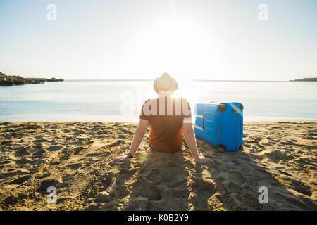 Mann in Sonnenbrille mit Gepäck auf dem Meer im Sommer sonnigen Tag - Stockfoto