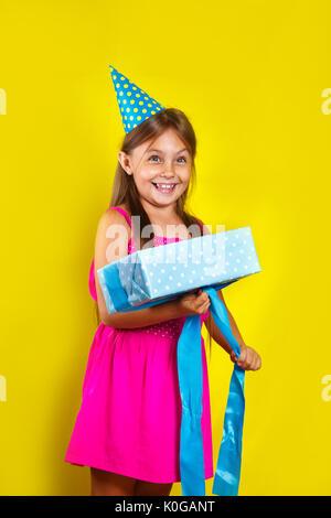 Geschenk auspacken. Studio Portrait von einem kleinen Mädchen das Tragen einer Partei hat auf ihrem Geburtstag. - Stockfoto