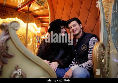 Junges Paar in Liebe auf einem Karussell zu einem fairen - Stockfoto