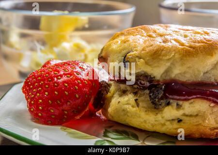 Obst Scone mit in Scheiben geschnittenen Erdbeeren auf der Seite mit Butter im Hintergrund - Stockfoto