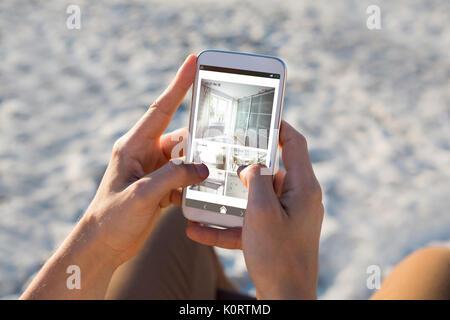 Innenraum der Küche und Schlafzimmer auf mobilen Bildschirm gegen die Hand des Menschen mit Handy am Strand - Stockfoto