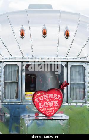 American Airstream Wohnwagen und ein Tunnel der Liebe Zeichen an einem Vintage Retro Festival. Großbritannien - Stockfoto