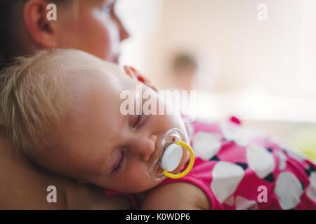Junge Mutter hält ihr schlafendes Neugeborenes - Stockfoto