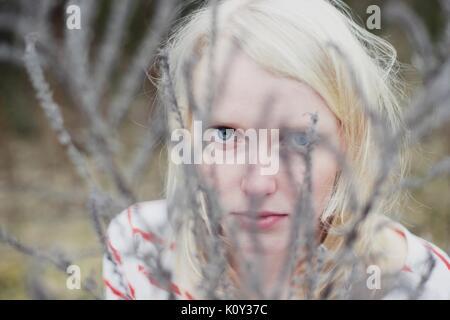 Frau hinter eine Zweigniederlassung, die in einem Wald - Stockfoto