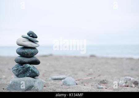 Monochrom, ruhigen, blauen gestapelte Steine auf einem Kalifornischen Strand als Symbol für Frieden, Gleichgewicht, - Stockfoto