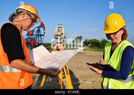 Zwei Gutachter bei der Arbeit und Erdöl Pumpe im Hintergrund - Stockfoto