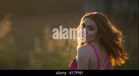 Porträt einer schönen jungen Frau, die in der Wiese bei Sonnenuntergang - Stockfoto