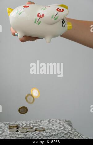Das Mädchen ist die Entleerung das Sparschwein. Spardose in Form einer lackiert Schwein. Eine Handvoll Münzen. - Stockfoto