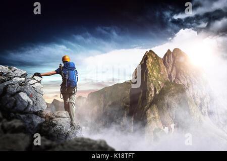Wanderer mit Rucksack erreicht den Gipfel eines Berges bei Sonnenuntergang. Erfolg, Freiheit und Glück, Erfolg in - Stockfoto