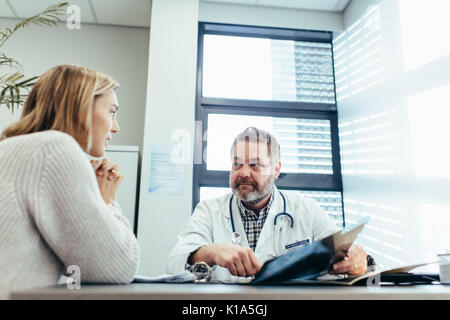 Männlicher Arzt in Kommunikation mit Patienten. Facharzt im Gespräch mit weiblichen Patienten während einer Anhörung - Stockfoto
