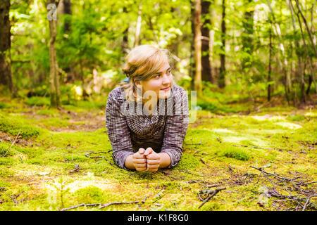 Junge Frau liegend auf moosigen Boden im Wald lächelnd Denken - Stockfoto