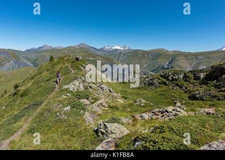Wanderer Frau zu Fuß auf den Weg in den Französischen Alpen Landschaft mit schneebedeckten Gipfeln im Hintergrund, - Stockfoto