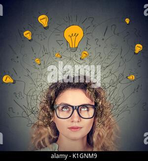 Ernsthafte Frau in Gläser mit vielen Ideen Lampen über dem Kopf suchen isoliert auf grauen Hintergrund. Eureka Kreativität - Stockfoto