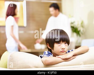 Asiatische Kind scheint traurig und unglücklich, während sich die Eltern streiten im Hintergrund. - Stockfoto