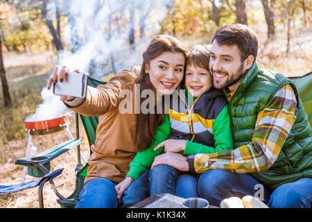 Glücklich lächelnde Familie Picknick Spaß und unter selfie im Herbst Park - Stockfoto