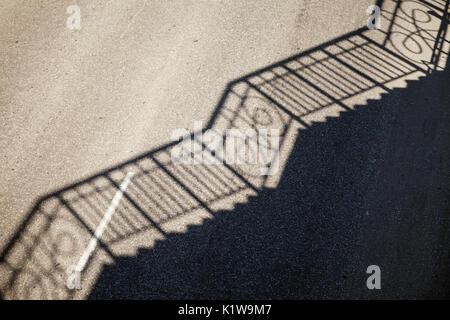 Geländer Schattenmuster auf einer leeren Straße Asphalt. Einfache industrielle Hintergrund