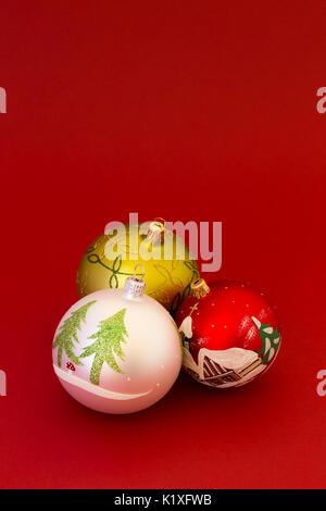 Schöne, weiße, rote und grüne Weihnachten Kugeln auf dunklen roten Hintergrund. - Stockfoto