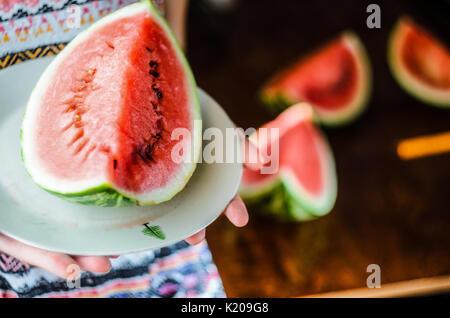 Wassermelone Hintergrund. Mädchen in einem bunten Sommer shirt Holding eine Platte mit einem großen Stück Wassermelone - Stockfoto