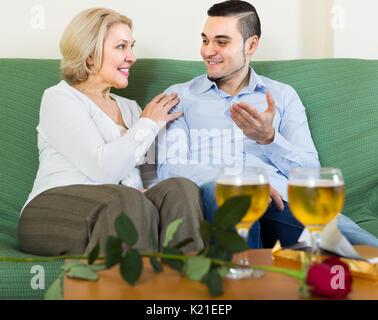 Happy senior reife Frau mit lächelnden jungen Freund Wein trinken zu Hause - Stockfoto