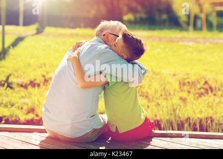 Großvater und Enkel umarmen am Liegeplatz - Stockfoto