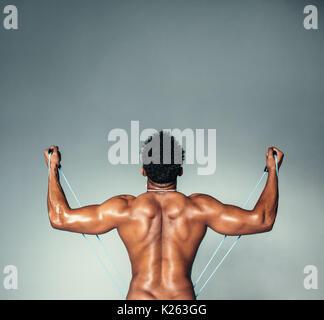 Ansicht der Rückseite Platz geschossen von Fitness männliches Modell mit fitnessband. Junger Mann Trainieren mit - Stockfoto