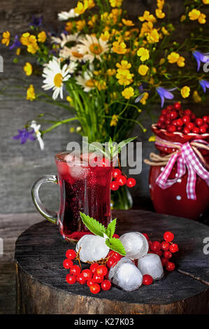 Frische natürliche Saft mit Eis und viburnum auf dem Hintergrund einer schönen Blumenstrauß von Wildblumen. - Stockfoto
