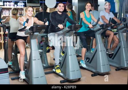 Aktive erwachsene Reiten Fahrräder in Fitness Club - Stockfoto