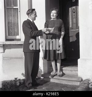 1964, historische, Bild zeigt einen elegant gekleideten Gentleman präsentiert einen Check an einen überrascht und - Stockfoto