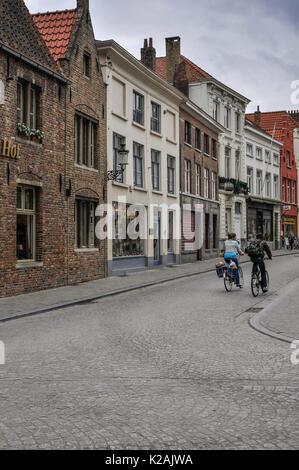 Ein paar Zyklus in einer ruhigen Straße mit Kopfsteinpflaster in der mittelalterlichen Stadt Brügge/Brügge, Westflandern, - Stockfoto