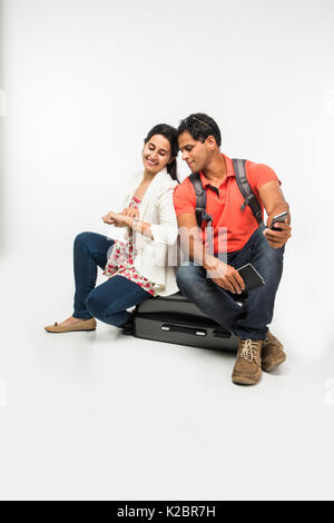 Indische Paar über gepackten Koffer sitzen, Warten auf Abflug mit Pässen in der Hand oder unter selfie. auf weißem - Stockfoto