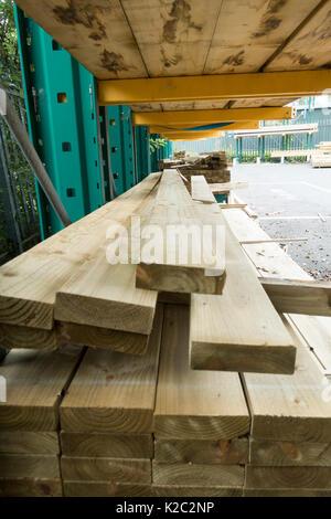 Gestapeltes Holz Regale an beliebten Gebäude Handel Händler Travis Perkins außerhalb unter der Abdeckung bei Winsford - Stockfoto