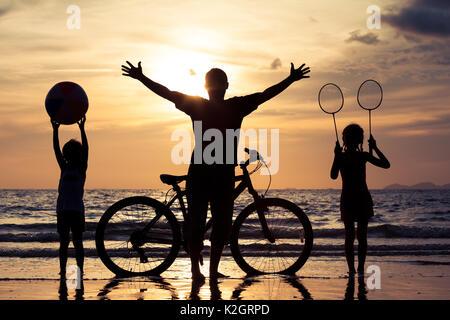 Vater und Kinder am Strand in den Sonnenuntergang spielen. Konzept der glücklichen Familie. - Stockfoto