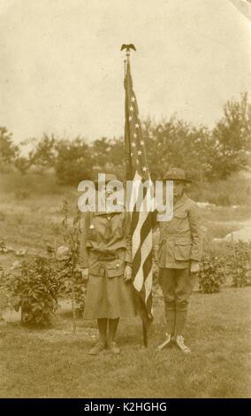 Antike c 1930 Foto, Pfadfinderinnen und Pfadfinder mit amerikanischer Flagge. Der Junge ist das Tragen von Converse - Stockfoto