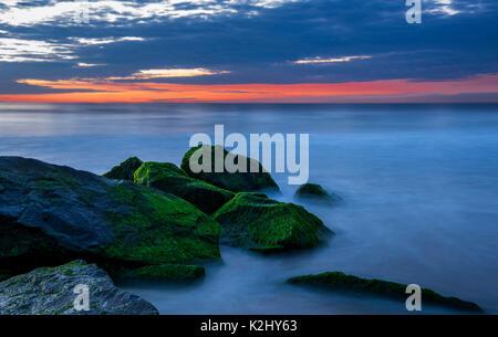Lange Belichtung Hintergrund während der Blauen Stunde, die das Wasser und die Steine im Vordergrund. - Stockfoto